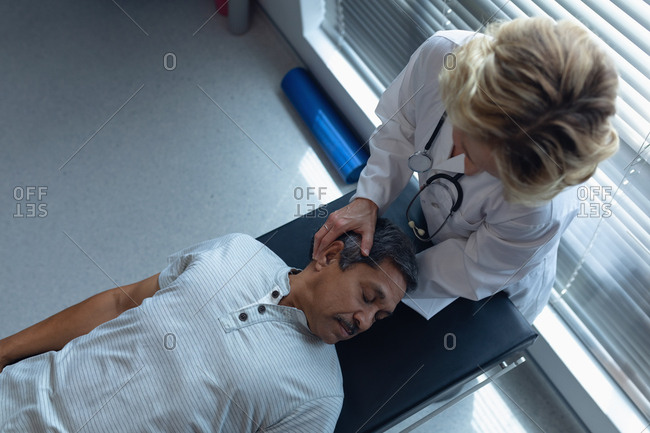 High angle view of Caucasian female doctor examining senior mixed-race male patient neck in hospital