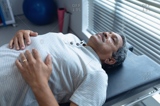 Side view of senior mixed race male patient lying on examining bed in hospital