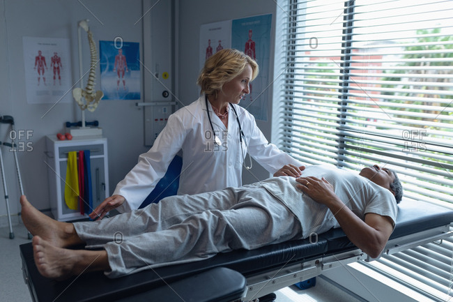 Front view of Caucasian female doctor examining senior mixed-race male patient in hospital