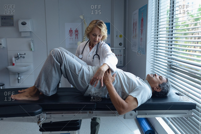 Front view of Caucasian female doctor examining senior mixed-race male patient back in hospital