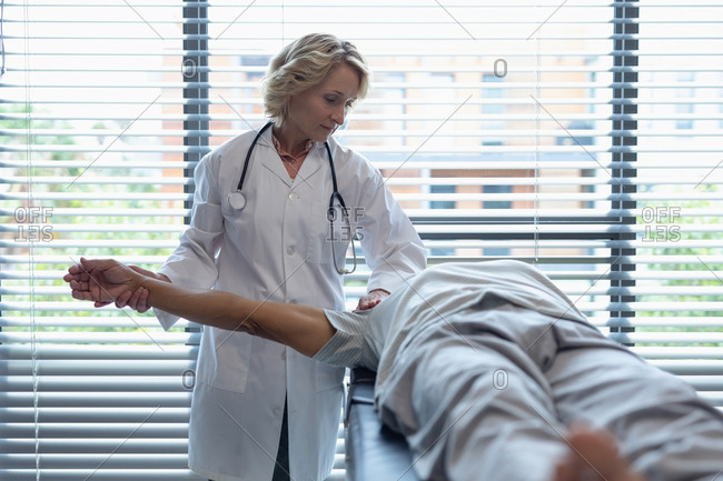 Front view of Caucasian female doctor examining senior mixed-race patient arm in hospital