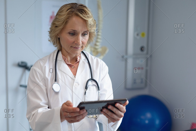 Front view of Caucasian female doctor with stethoscope around her neck using digital tablet in the hospital