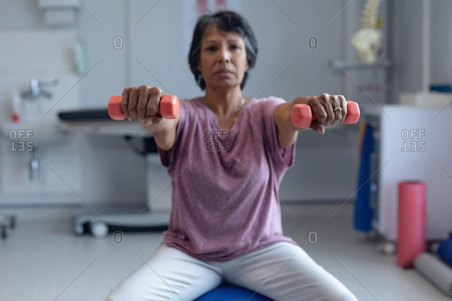 Front view of mixed-race female patient exercising with dumbbells on exercise ball in the hospital