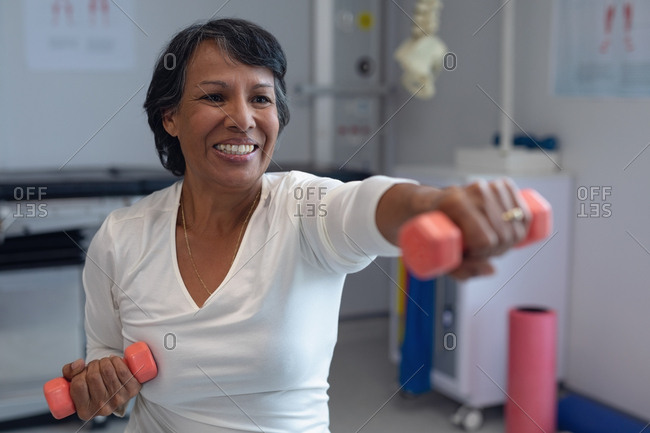 Front view of mixed-race female patient exercising with orange dumbbells in the hospital