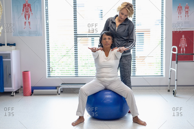 Front view of Caucasian female physiotherapist helping mixed-race female patient on exercise ball in the hospital