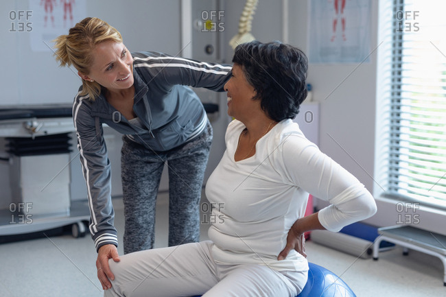 Side view of Caucasian female physiotherapist helping mixed-race female patient on exercise ball in the hospital