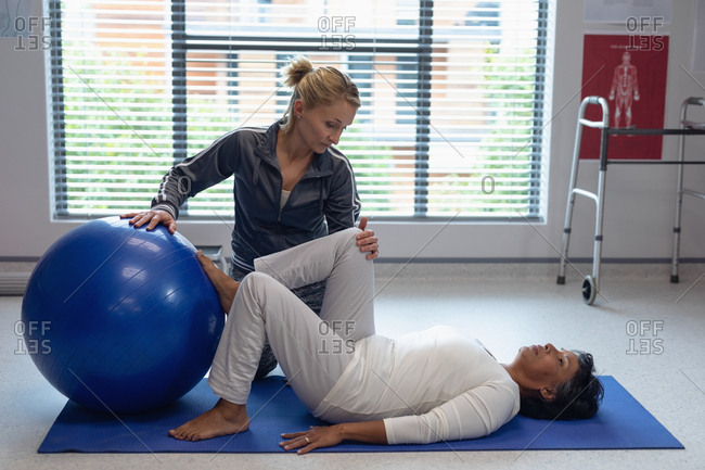 Side view of Caucasian female physiotherapist helping mixed-race female patient with exercise on exercise ball in the hospital.