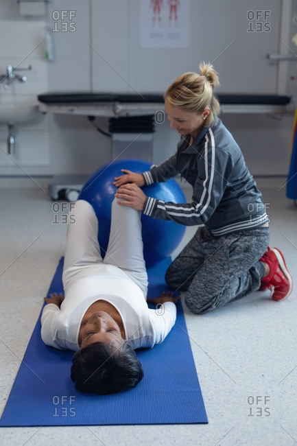 Side view of Caucasian female physiotherapist giving physical therapy to mixed-race female patient on exercise ball in the hospital