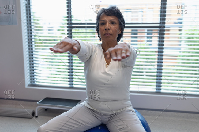 Front view of mixed race female patient exercising on exercise ball in the hospital