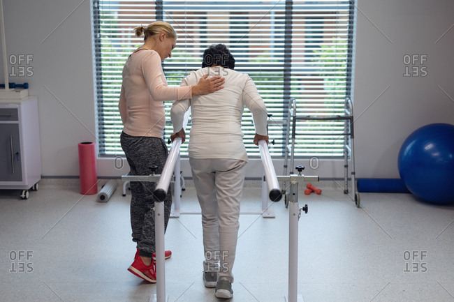 Rear view of Caucasian female physiotherapist helping mixed-race female patient walk with parallel bars in the hospital