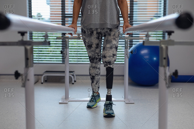 Low section of Caucasian female amputee patient walking with parallel bars in hospital