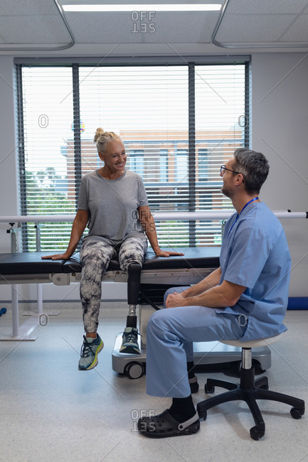 Side view of happy Caucasian male physiotherapist talking with disable female patient in hospital