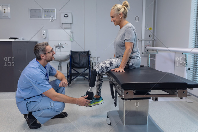 Side view of Caucasian male physiotherapist adjusting prosthetic leg of female patient in hospital