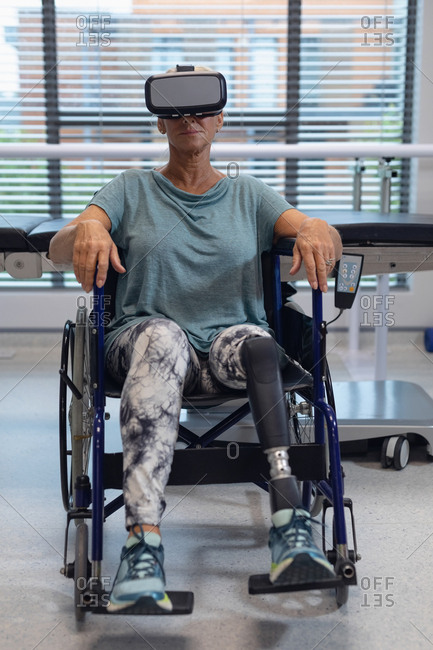 Front view of disabled Caucasian female patient using virtual reality headset in wheelchair in the hospital