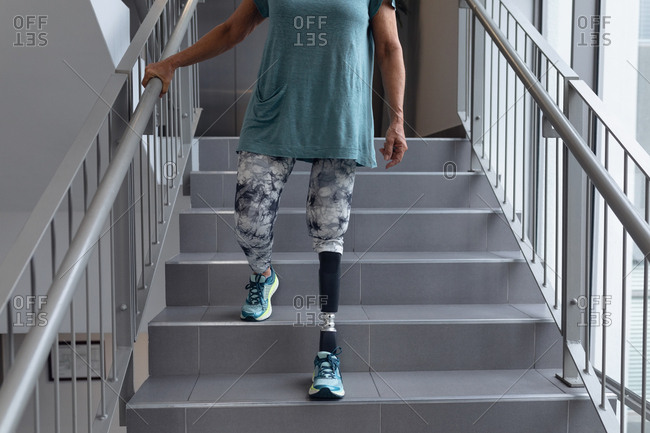 Low section of disabled Caucasian female patient with prosthetic leg walking on stairs in hospital