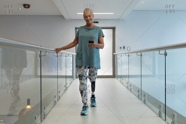 Front view of disabled Caucasian female patient with prosthetic leg using mobile phone while walking in corridor at hospital