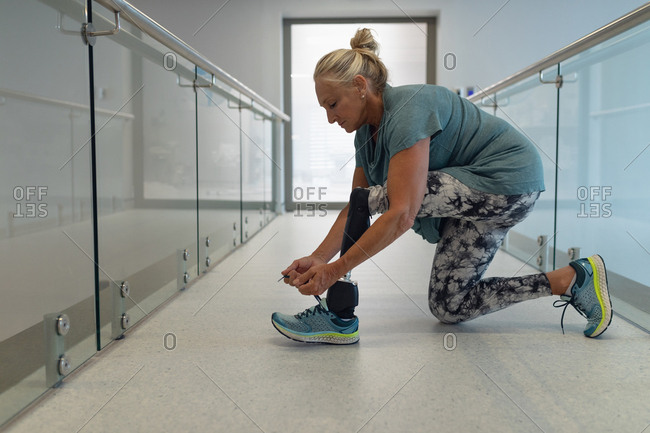 Side view of disabled Caucasian female patient with prosthetic leg tying shoelace in corridor at hospital