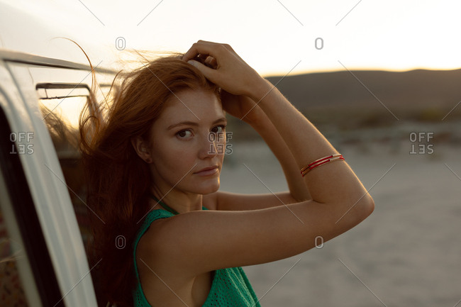 Side view of beautiful Caucasian woman looking at camera while leaning on camper van at beach