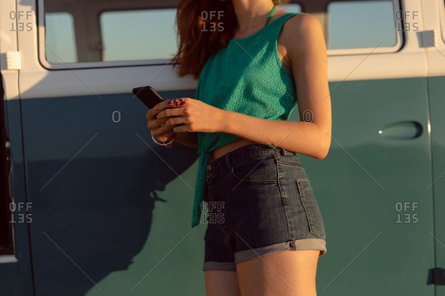 Mid section of Caucasian woman leaning on camper van and using mobile phone at beach