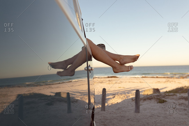 Low section of Caucasian woman relaxing with feet up in a camper van at beach