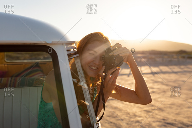 Front view of young Caucasian woman taking picture with digital camera out of window of a camper van
