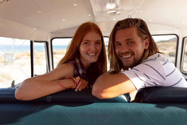 Portrait of happy young Caucasian couple looking at camera in front seat of camper van at beach