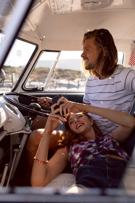 Front view of beautiful Caucasian woman using mobile phone while lying on man's lap in front seat of camper van at beach