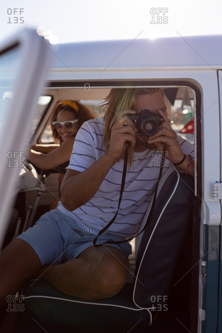Front view of young Caucasian man taking pictures with digital camera in front seat of camper van at beach. Mixed race woman smiling in the background