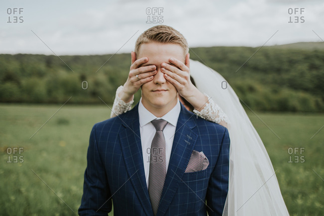 Portrait of young groom waiting on meadow and bride standing behind him covering his eyes.