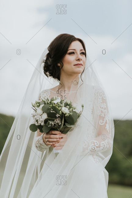 Young bride wearing elegant wedding gown looking into distance.