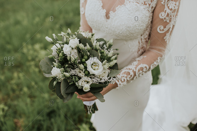 Cropped image of bride holding elegant wedding bouquet of white roses.