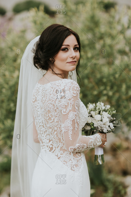 Portrait of young bride wearing elegant lacey wedding gown looking into camera.