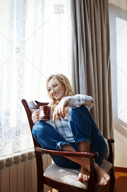 Woman drinking coffee and relaxing on armchair