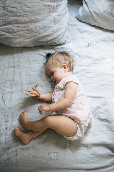 Portrait of a baby girl lying down on a bed looking at a necklace in her hand