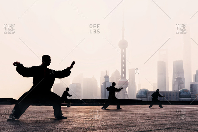 March 30, 2019: Silhouette of a group of people practicing Tai Chi in The Bund at sunrise, Shanghai, China
