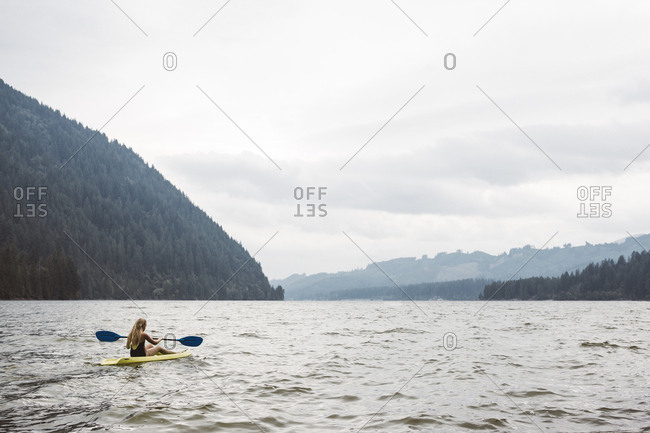 Young girl rowing a kayak in a lake
