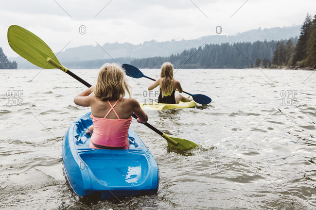 Two young girls rowing kayaks in a bay on a cloudy day