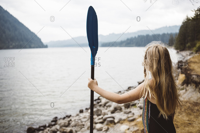 Young blonde girl looking across a lake holding an oar