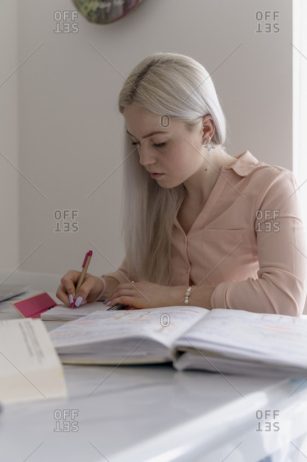 Young woman studying at home for a university exam
