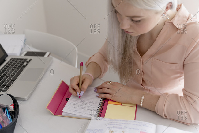Young blonde woman studying at home for a university exam