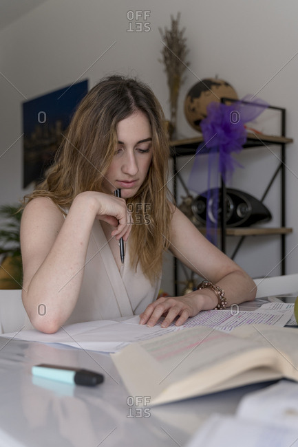 Young woman studying for a university exam at home