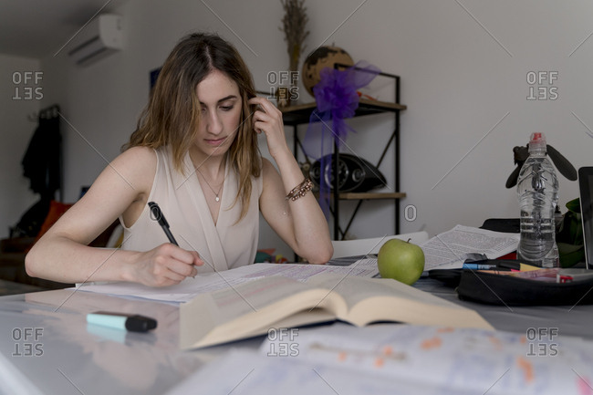 Young brunette woman studying for a university exam at home