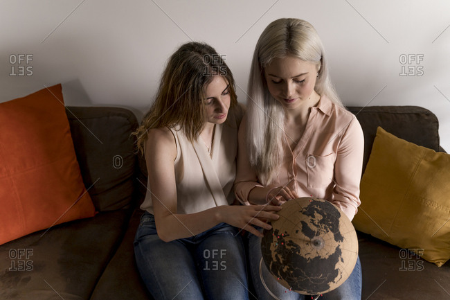 Two young women looking at the globe for the next travel