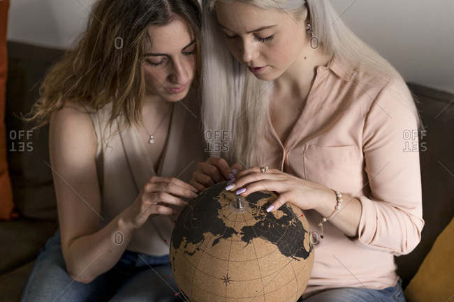 Two young women looking at a globe