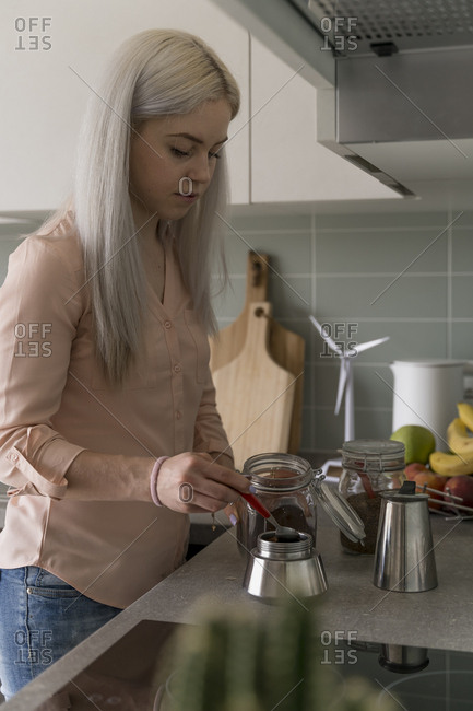 Blonde young woman preparing coffee at home