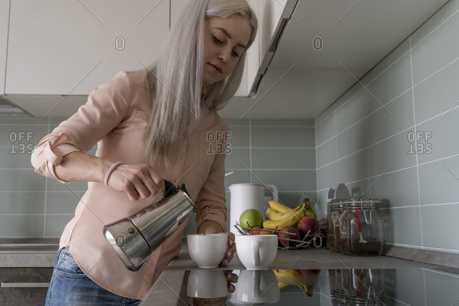 Young blonde woman pouring coffee at home