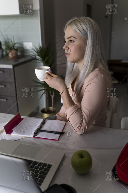Young woman studying at home for a university exam and drinking coffee
