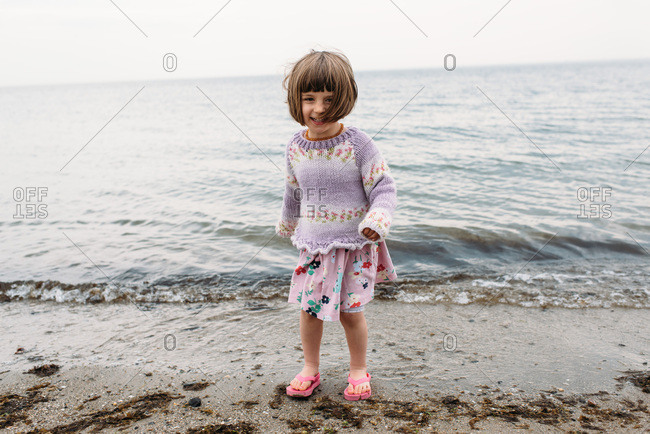 Happy little girl walking by the water's edge at a New England beach