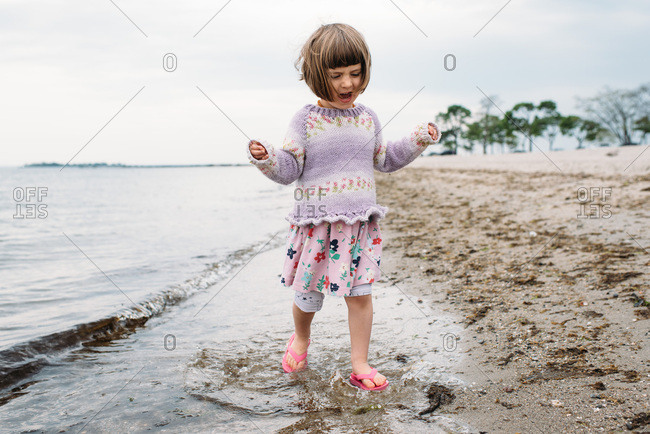 Little girl walking by the water's edge at a New England beach