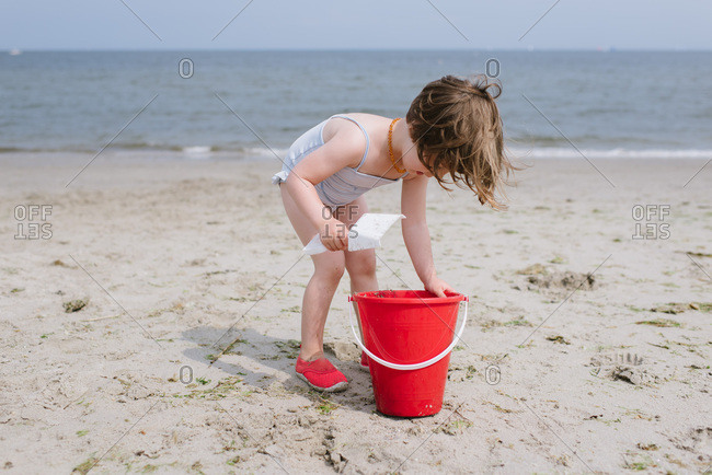 Little girl playing in sand at the beach with a red bucket and shovel